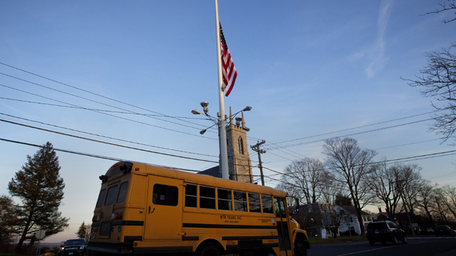A flag is seen at half mast as a school bus passes along Main Street in Newtown, Connecticut