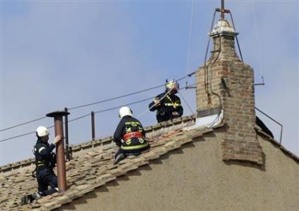 Members of the fire and rescue service set a chimney on the roof of the Sistine Chapel at the Vatican