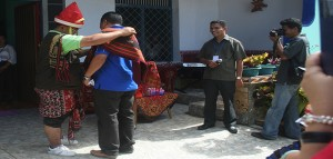 Pastor Yustinus Guru Kedi mengalungkan selempang di bahu Sekretaris Eksekutif Komsos KWI Pastor Kamilus Pantus saat tiba di Sumba