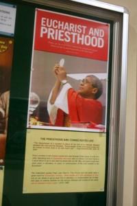 Imam pastor dan ekaristi dalam sebuah poster di Gereja Christ the King of Singapore ok